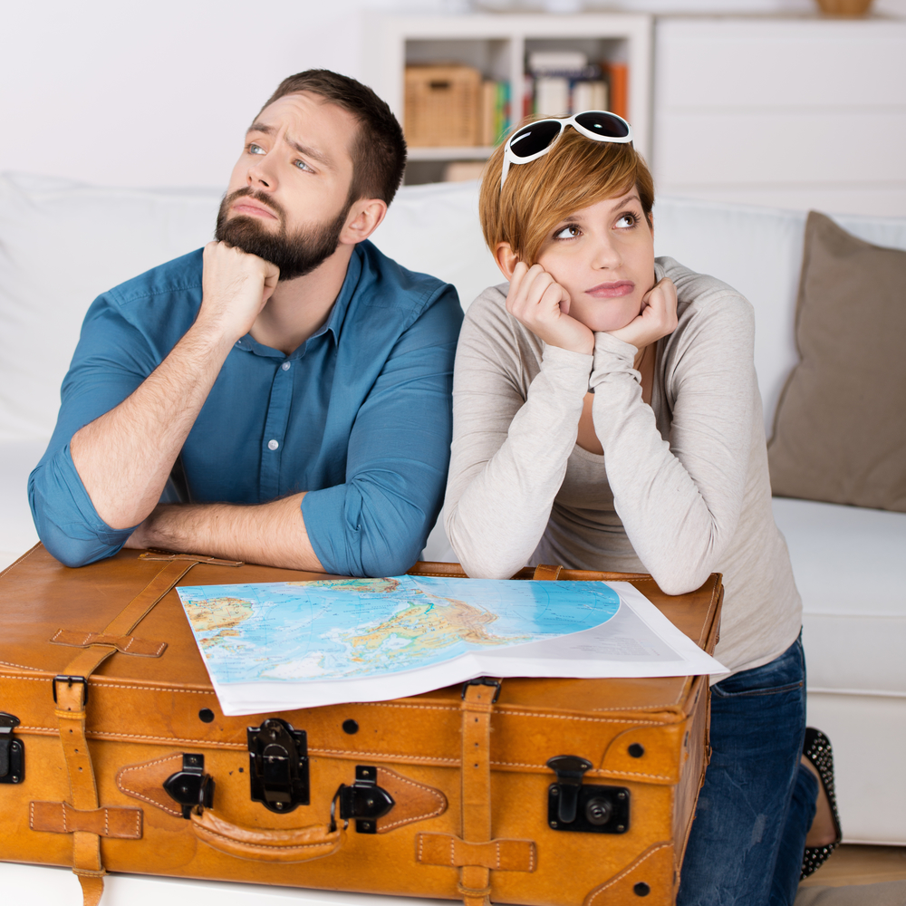 couple leaning on suitcase looking at home
