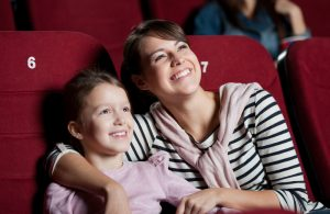 mother and daughter laughing in the theatre