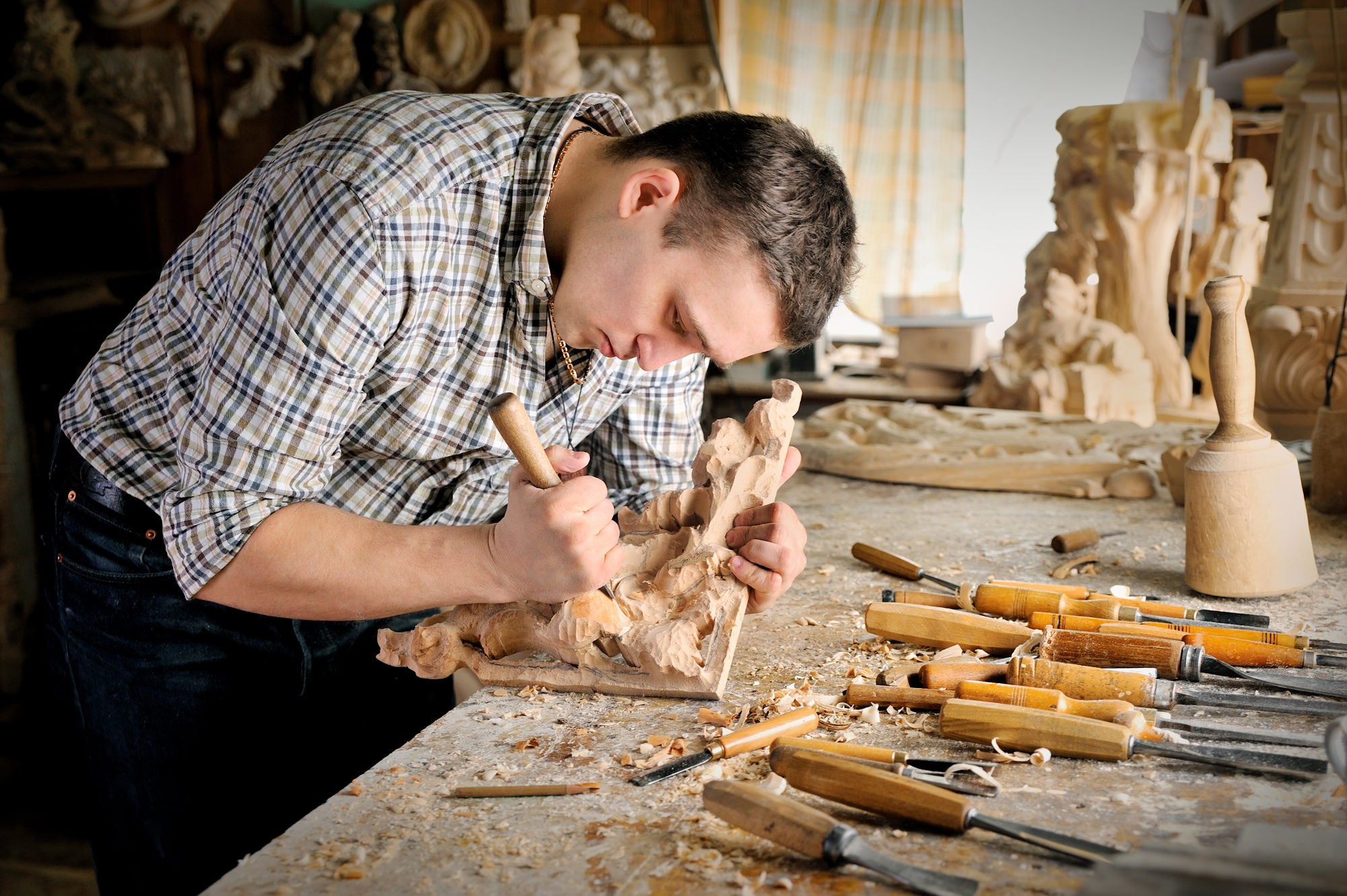Young man carving wood in his man shed