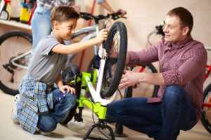 father and son repairing bicycle in self-storage unit